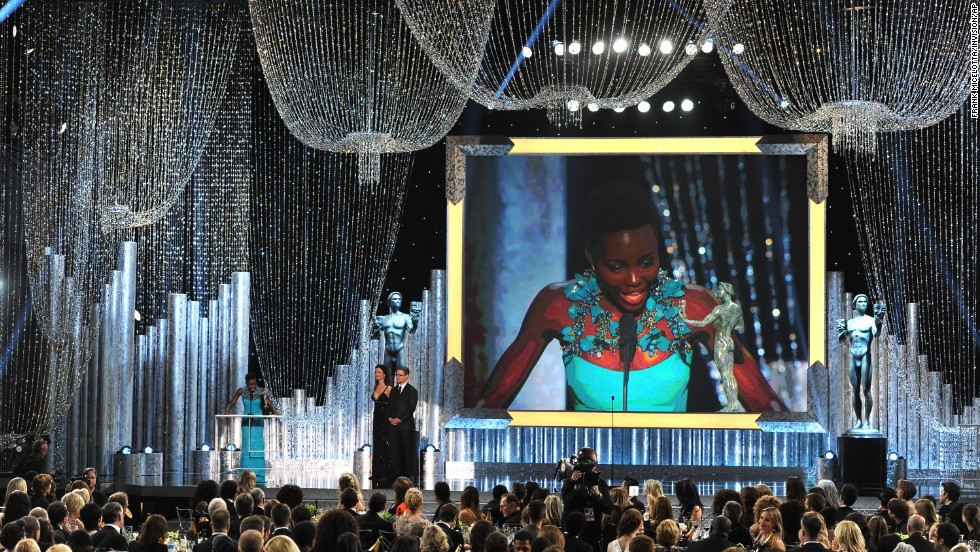 "Lupita Nyong'o accepts the award for outstanding performance by a female actor in a supporting role for her part in ""12 Years a Slave."""