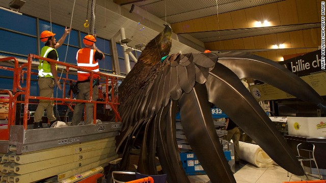 Workers secure a giant eagle sculpture after it fell from the roof of Wellington Airport during a 6.2-magnitude earthquake.
