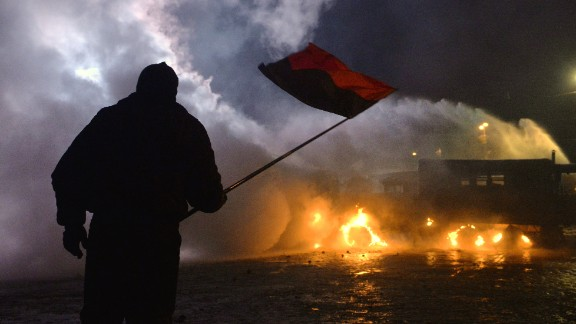 A protester waves a flag during the clash with police in the centre of the Ukrainian capital Kiev on January 20, 2014, after 200,000 turned up for an opposition rally in a show of defiance against strict new curbs on protests