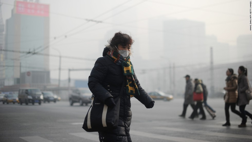 A  woman wears a face mask on January 16 as thick smog cuts visibility in the Chinese capital. China has seen a huge increase in coal-burning power plants, and its manufacturing practices aren't nearly as efficient as in the West.