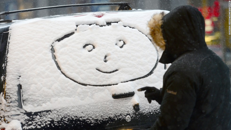 A person draws a happy face in the snow on a car window in New York.
