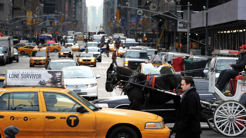A horse pulls a carriage between cars and cabs along 59th Street in January 2014.