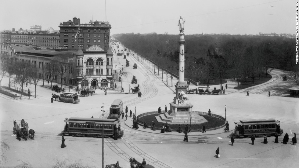 Trolley cars, pedestrians and horse-drawn carriages negotiate the traffic around Columbus Circle at the southwest corner of Central Park in the late 1900s.