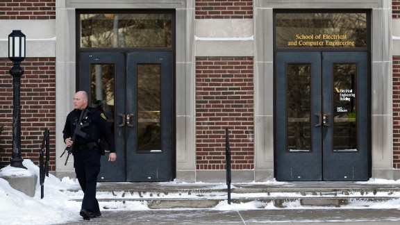 A police officer walks out of the electrical engineering building on the Purdue University campus.