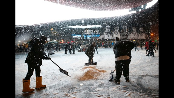 Workers shovel snow in front of Barclays Center in Brooklyn, New York, on January 21 before an NBA game between the Orlando Magic and Brooklyn Nets.