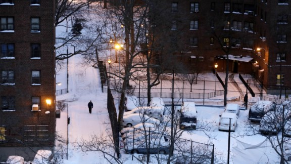 A man makes his way on a snow-covered path between apartment buildings in New York on January 22.
