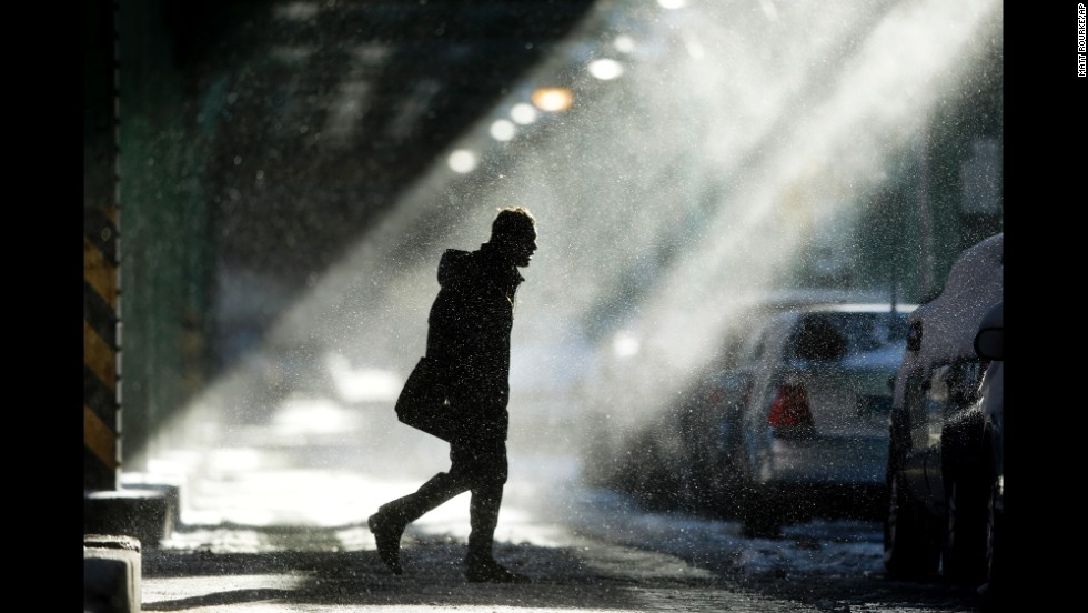 Windblown snow swirls around a man under elevated train tracks in Philadelphia on Wednesday, January 22.