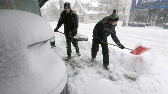 Tommy Mallios, left, and his brother Evan shovel snow from a sidewalk in Scituate, Massachusetts, on January 22.