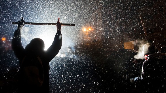 Protesters clash with police in Kiev as snow falls on January 22.