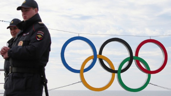 Police officers pass the logo in the olympic park opened for the 2014 Winter Olympic Games in Sochi on January 7, 2014, in Sochi, Russia.