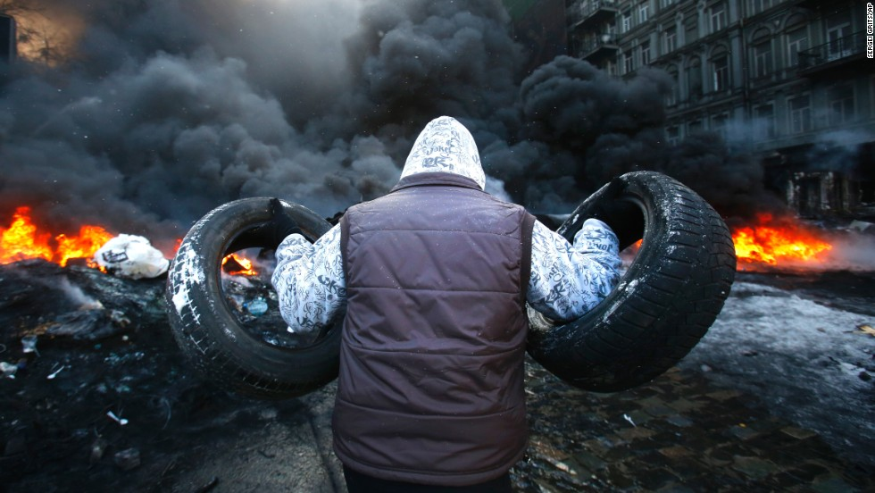 A protester carries tires toward a fire on January 23.