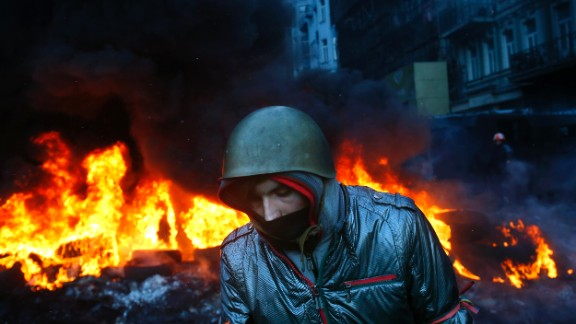 A protester walks pass burning tyres in central Kiev, Ukraine, Thursday Jan. 23, 2014.