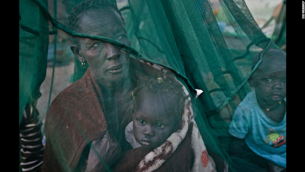 One of the few to have a mosquito net, a displaced family who fled the recent fighting between government and rebel forces in Bor by boat across the White Nile, sit under it in Awerial, South Sudan, on Thursday, January. 2.