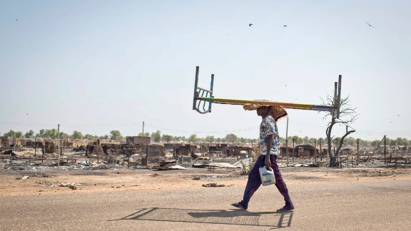 A young man balances a bed on his head as he walks through empty streets and destroyed buildings after government forces retook from rebel forces the provincial capital of Bentiu, in Unity State, South Sudan, on Sunday, January 12.