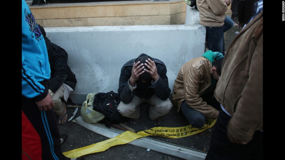 Egyptian police officers sit on the street after the blast.