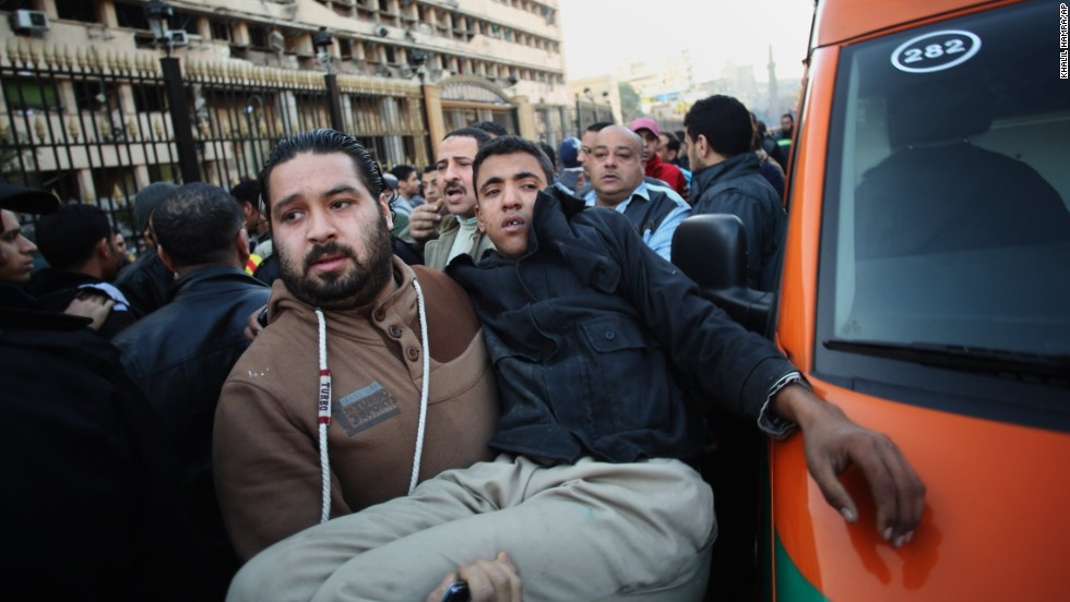 A man carries an Egyptian police officer to an ambulance after a car bomb explosion at the police headquarters in downtown Cairo on Friday, January 24.