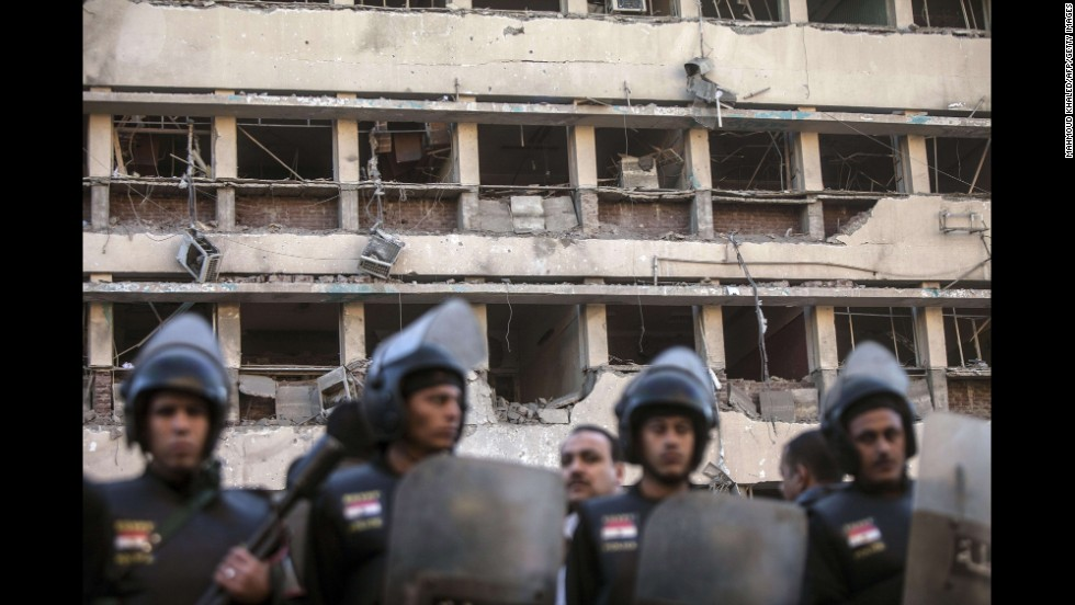 Police stand in front of the damaged facade of the Cairo police headquarters.