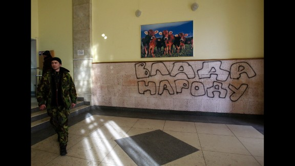 """A protester passes past graffiti that reads """"Government for People"""" in the Ministry of Agricultural Policy building in Kiev on January 24."""