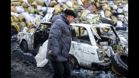 A man walks past the wreckage of a car on January 24.