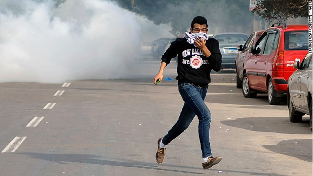 An Egyptian supporter of the Muslim Brotherhood escapes from tear gas during clashes with Egyptian police in the northern port city of Alexandria on January 23, 2014.