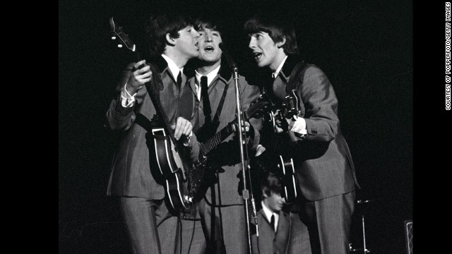The Beatles 1964 US Tour, L-R: Paul McCartney, John Lennon and George Harrison share a microphone as they sing a song in concert at Carnegie Hall in New York during the band's tour of America  (Photo by Popperfoto/Getty Images)