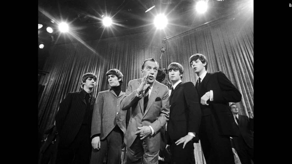 "Television host Ed Sullivan, center, stands with The Beatles on February 9, 1964, during a rehearsal for the band's appearance on ""The Ed Sullivan Show."" The iconic television appearance remains one of the highest-rated nonsports programs of all time. Nielsen estimated that 45% of the country watched the show -- more than 73 million people then."