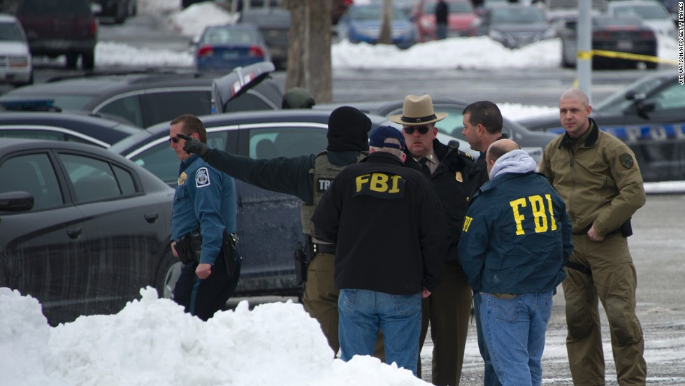 Police and FBI agents meet outside the mall.