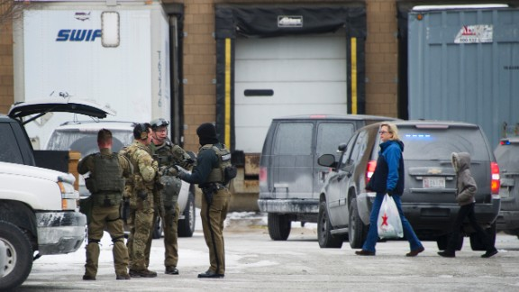 Maryland State Police officers gear up as civilians depart Columbia Mall after the shooting.