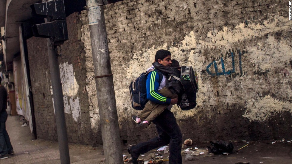 A man carries his son to escape clashes between police and anti-military protesters.
