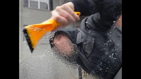 Kyle Malott scraps the ice off his girlfriend's car near Covington, Louisiana, on January 24.