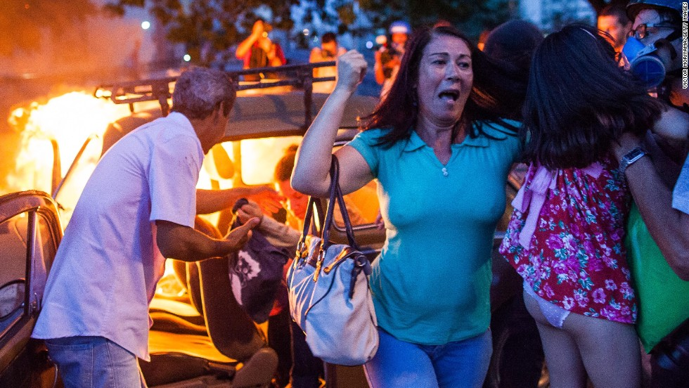 People help a family out of a burning car after it drove over a barricade set on fire by protesters on Saturday, January 25. Brazil saw nationwide demonstrations against staging the World Cup after activists from the protest group Anonymous went on social media calling for action. While most of the protests in other Brazilian cities remained peaceful, the Sao Paulo event turned violent.