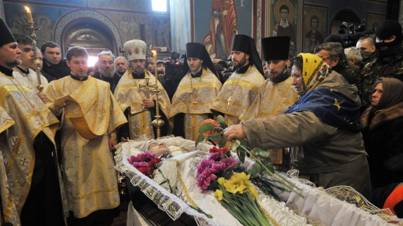 Orthodox priests lead the funeral service for slain protester Mikhail Zhiznevsky in Kiev on Sunday, January 26.