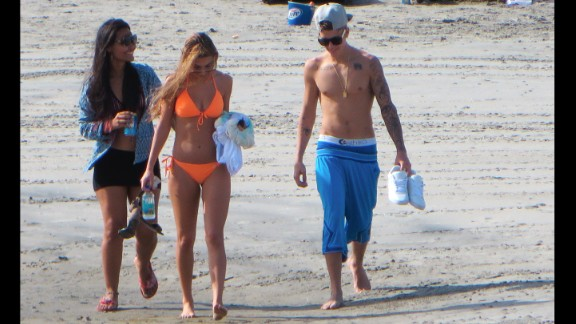 Justin Bieber walks on a beach in Panama on Saturday, January 25, two days after he was charged in Miami with drunken driving, resisting arrest and driving without a valid license. The pop star is accompanied by his new girlfriend, model Chantel Jeffries, who is wearing the orange bikini.
