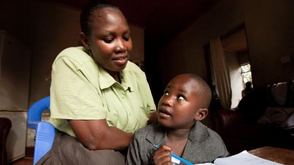 Tatu Msangi, who is HIV-positive, works on homework with virus-free daughter Faith.