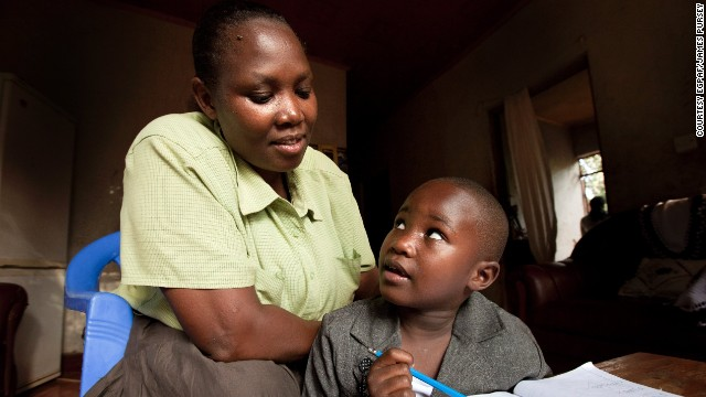 Tatu Msangi, who is HIV-positive, works on homework with virus-free daughter Faith.