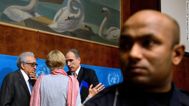 A security officer stands guard as UN-Arab League envoy for Syria Lakhdar Brahimi speaks with UN staff at the United Nations Offices in Geneva on January 26, 2014.