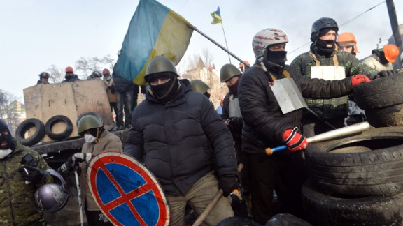 An anti-government protester holds a road sign as a shield as demonstrators guard a barricade in central Kiev on January 27, 2014