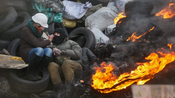 A couple warms themselves near a fire at a barricade in Kiev on January 27.