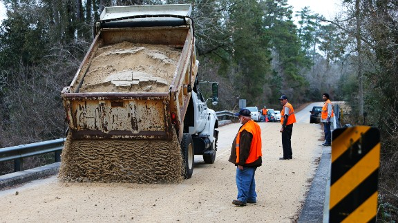 Workers dump sand across a bridge in Covington, Louisiana, on January 27.
