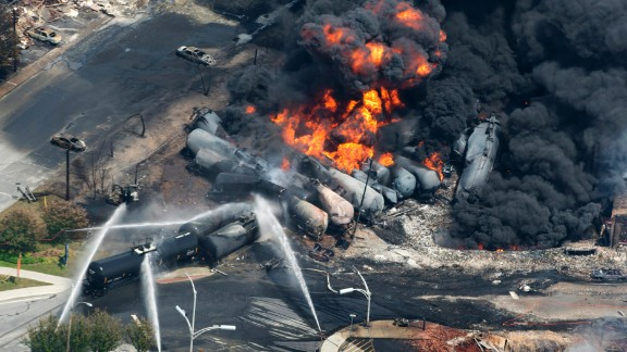 Smoke rises from railway cars after a train derailed in Lac-Megantic, Quebec, Canada, on July 6, 2013. A large swath of Lac-Megantic was destroyed after the derailment sparked several explosions. The train was carrying crude oil. At least 42 of the community