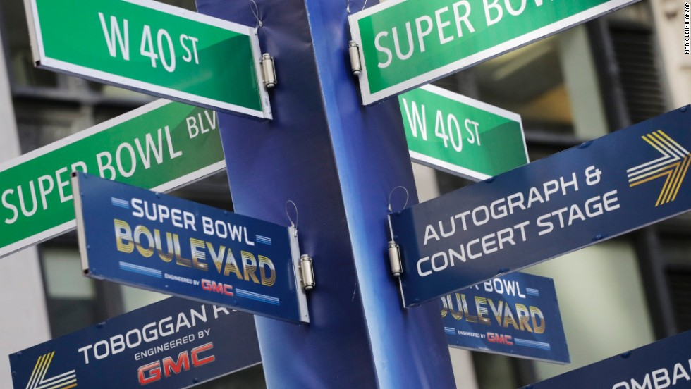 Street signs point to Super Bowl attractions in Times Square. Several blocks of Manhattan have been converted into a temporary festival space.