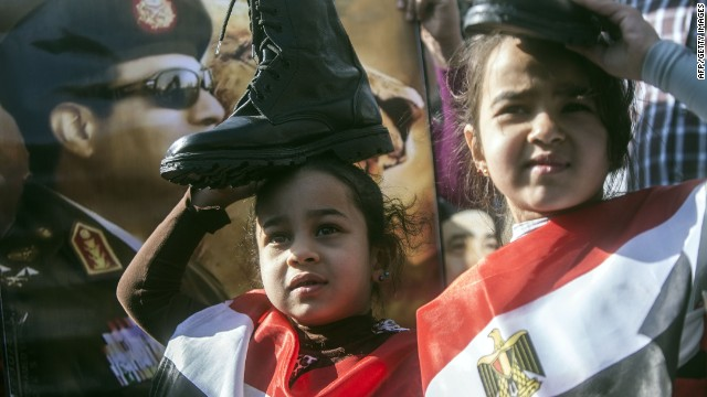 Supporters of Egypt's army chief Field Marshal Abdel Fattah al-Sisi (portrait), who is to run for the presidency in the upcoming elections, hold military boots on their heads in a sign of support for military rule, as they wear the Egyptian flag, during a demonstration outside the Police Academy in Cairo where a new hearing in the trial of deposed president Mohamed Morsi opened on January 28, 2014