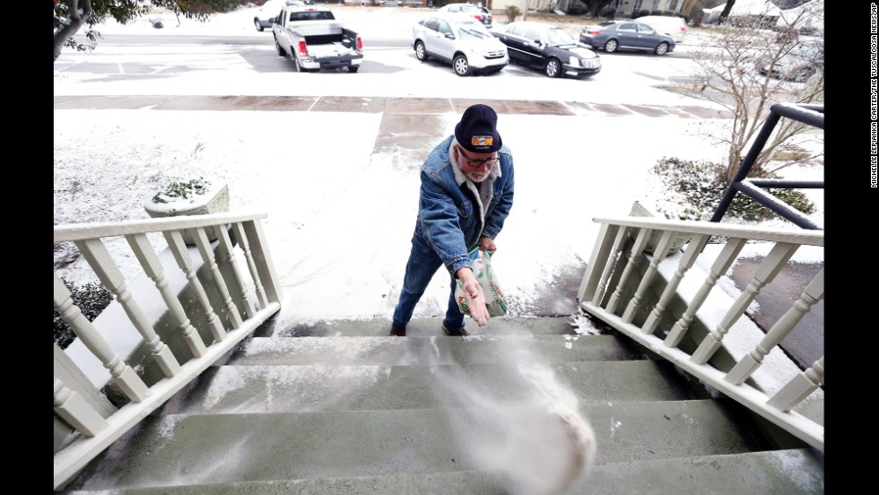 A man puts sand on the steps of his business in downtown Northport, Alabama, on January 28. Northport is near Tuscaloosa in the central-west part of the state.