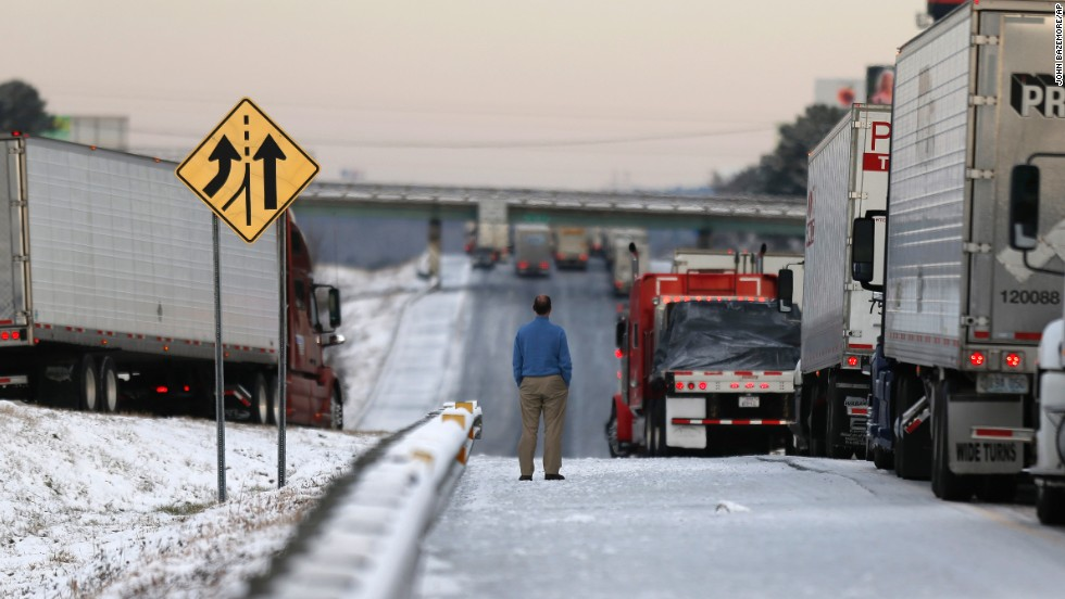 A man stands on the frozen roadway January 29 as he waits for traffic to clear along Interstate 75 in Macon, Georgia.