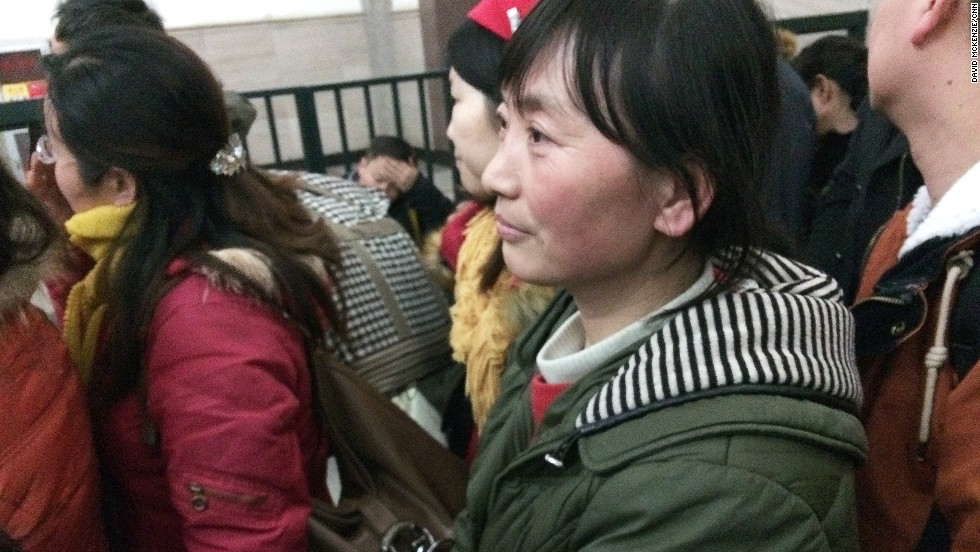 Zhou waits with hundreds of people crowding to get on the  overnight T63 train to Hefei. While China has a growing network of high-speed trains, the T63 is old rolling stock and travels at a slower pace.