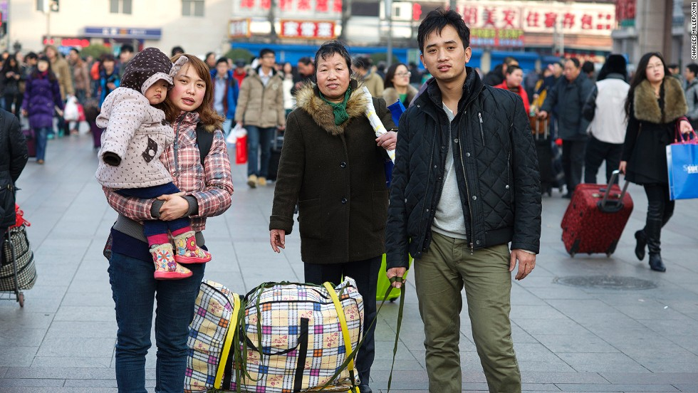 Cai Dongping (R) came to Beijing from Southern China's watery city of Shaoxing in Zhejiang province six years ago. He works in a factory assembling home electronic devices. Cai's wife is holding their three-year-old child and his mother accompanies them.
