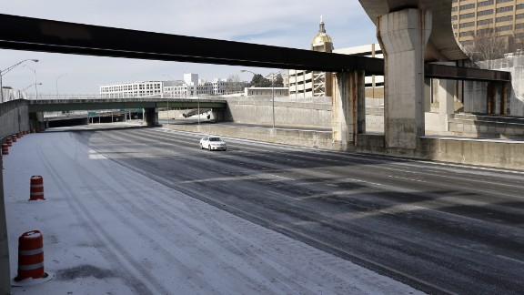 A lone car travels on Interstate 75/85 in downtown Atlanta on January 29, a day after the roadway was packed with vehicles.