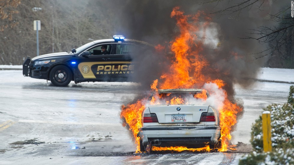 Police monitor a fire January 29 in a vehicle left overnight by a motorist who was stranded in Brookhaven, Georgia.