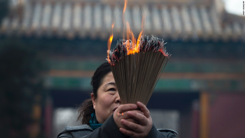A woman holding incense prays at the Yonghegong Lama Temple. In China, the festivities are also known as the spring festival.