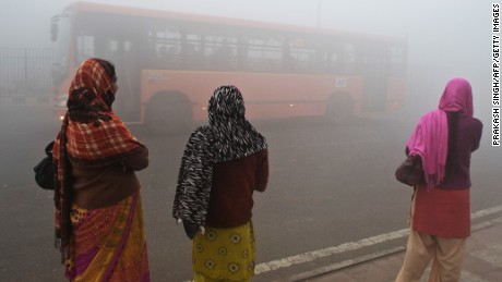 Indian commuters wait for a bus on a polluted morning in New Delhi.